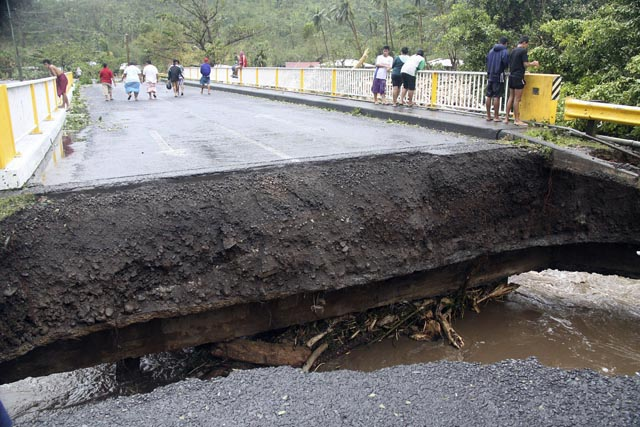 People walk over a destroyed bridge in Samoa's capital Apia, Friday, Dec. 14, 2012