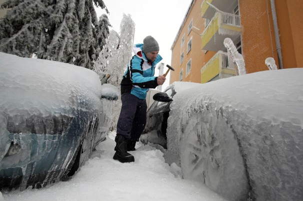 A man chips the ice off his car in Postojna, Slovenia